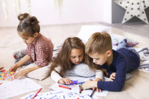 Three focused children are playing on the floor and drawing in coloring books